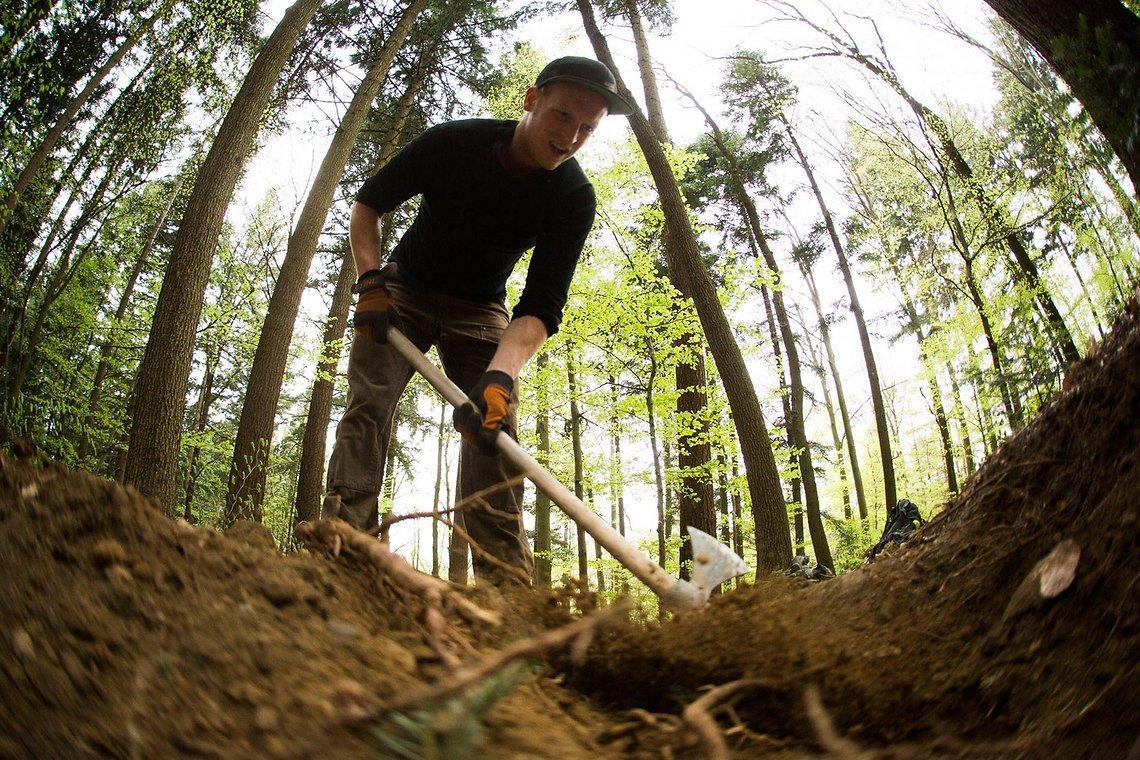 Trailbau auf die konventionelle Art. Die Anlieger in den Hang fräsen, Steine und Wurzeln beseitigen und fertig ist der Traum jedes Stollenreifenbergabfahrradfahrers.
