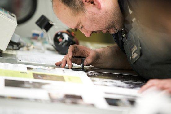 Der Drucker überprüft die Farbgebung und die Passermarken, so dass alle vier Farben exakt aufeinanderpassen.