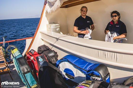 Die Crewmitglieder Serjan und Adam an Deck, das schon die ganze Woche von Evoc-Bags überflutet ist